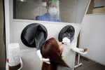 A healthcare worker takes a nasal swab sample for a for COVID-19 test from inside a freestanding isolation booth at a hospital in Buenos Aires, Argentina, Monday, Oct. 19, 2020. (AP Photo/Natacha Pisarenko)