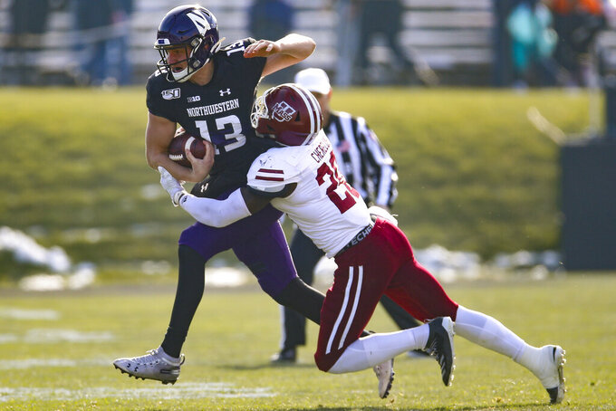 Northwestern's Jason Whittaker, left, is tackled by Massachusetts' Claudin Cherrelus during the first half of an NCAA college football game Saturday, Nov. 16, 2019, in Evanston, Ill. (AP Photo/Jim Young)