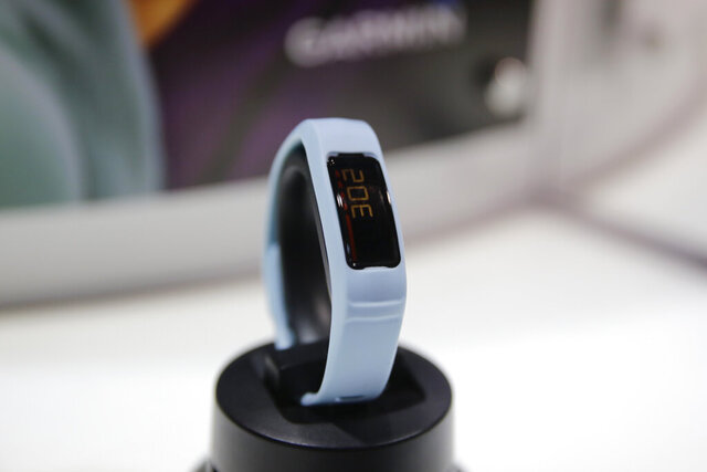 FILE - In this Jan. 7, 2015 file photo, Garmin's Vivofit 2 fitness tracker is on display at the Garmin booth at the International CES, in Las Vegas. GPS device-maker Garmin's online fitness tracking service has gone down, leaving runners and cyclists struggling to upload data from their latest workouts. Garmin Connect, an app and website that works with the company's popular line of fitness watches, remained out of service on Friday, July 24, 2020. (AP Photo/Jae C. Hong, File)