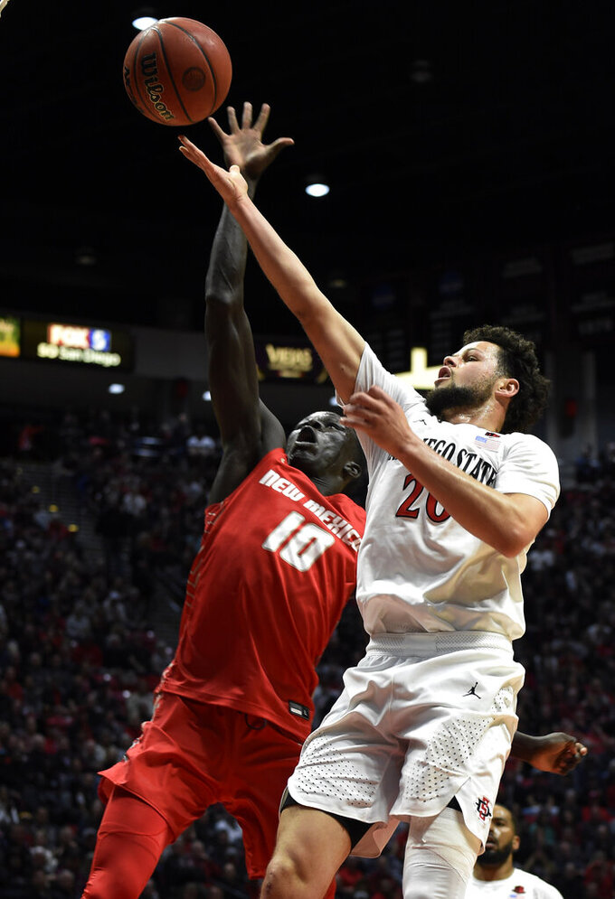 San Diego State guard Jordan Schakel (20) shoots over New Mexico guard Makuach Maluach (10) during the first half of an NCAA college basketball game, Tuesday, Feb. 11, 2020, in San Diego. (AP Photo/Denis Poroy)