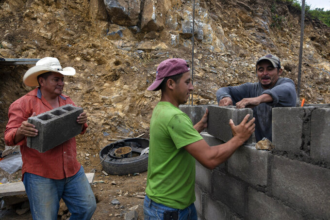 Ivan Varela carries a cinder block as he helps day laborers lay brick for a new home for his parents, who were left homeless in November 2020 when their house was obliterated by a mudslide triggered by Hurricanes Eta and Iota, at the construction site in Mission San Francisco de Asis Honduras, Thursday, July 15, 2021. Each family must send one person to work on the construction of their home. They do not receive wages and if they don't work, they must pay into a kitty about $6 a day (150 lempiras). (AP Photo/Rodrigo Abd)