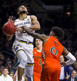 Notre Dame's Prentiss Hubb, left, gets fouled under the basket by Miami's Chris Lykes (0) during the second half of an NCAA college basketball game Sunday, Feb. 23, 2020, in South Bend, Ind. (AP Photo/Robert Franklin)