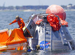 FILE - In this July 13, 2017, file photo, NASA astronaut Mike Fincke jumps into a life raft from an Orion capsule the astronauts are using for a recovery test about four miles off of Galveston Island, Texas in the Gulf of Mexico, the first time since the Apollo program that NASA has practiced such egress techniques from a capsule in open water. Astronaut safety is paramount in getting to the moon, according to NASA Administrator Jim Bridenstine. But speed and cost are close seconds. By moving up the target lunar landing date from 2028 to 2024, NASA hopes to retire as much political risk as possible by getting out of the gate fast. (Mark Mulligan/Houston Chronicle via AP, File)