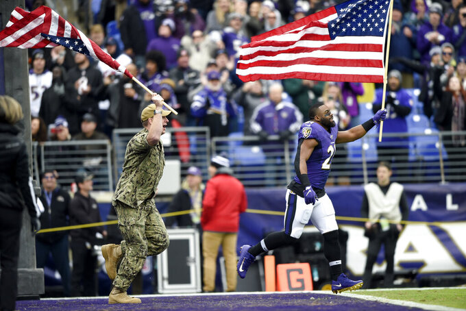 Baltimore Ravens running back Mark Ingram (21) and a U.S. service member run with flags as part of the team's Salute to Service prior to an NFL football game against the Houston Texans, Sunday, Nov. 17, 2019, in Baltimore. (AP Photo/Gail Burton)