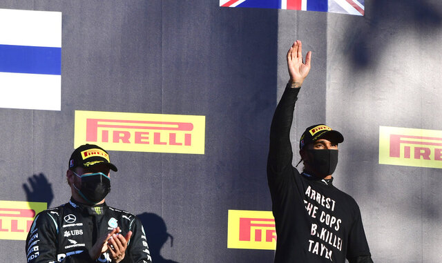 Winner of the race, Mercedes driver Lewis Hamilton of Britain, right, waves as he stands with second place Mercedes driver Valtteri Bottas of Finland on the podium during the Formula One Grand Prix of Tuscany, at the Mugello circuit in Scarperia, Italy, Sunday, Sept. 13, 2020. (Jennifer Lorenzini, Pool via AP)