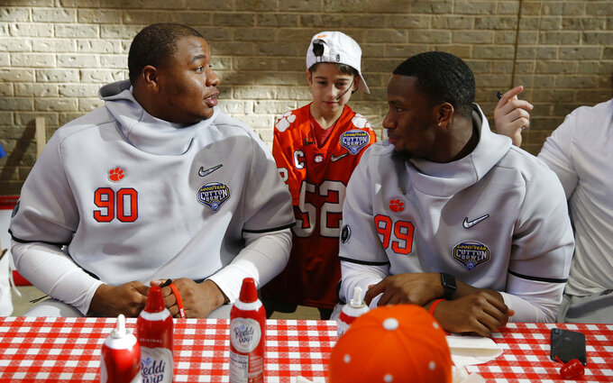 Clemson defensive tackle Dexter Lawrence, left, and defensive end Clelin Ferrell talk as honorary captain Layton Horner, center, stands by during a hospital visit at Texas Scottish Rite Hospital in Dallas, Thursday, Dec. 27, 2018. Clemson will play against Notre Dame in the Cotton Bowl on Saturday. (Vernon Bryant/The Dallas Morning News via AP)