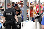 FILE - In this Feb. 16, 2020, file photo, Secret Service Agents search fans as they enter the Fan Zone before the NASCAR Daytona 500 auto race at Daytona International Speedway in Daytona Beach, Fla. NASCAR's season started with secret service doing a security check on the firesuit-clad pole-sitter for the Daytona 500 and thousands of fans waiting hours in line to pass through a metal detector for the big kickoff. When it resumes this Sunday, May 17 — four races and 13 weeks later — drivers will have their temperature taken as they enter the track, they will be wearing masks as they leave their isolated motorhomes and make their way to their cars. There will be no fans at Darlington Raceway.  (AP Photo/John Raoux, File)