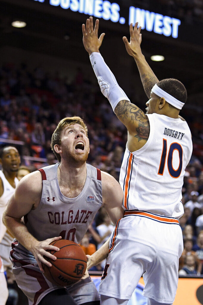 Colgate forward Will Rayman, left, looks to shoot while defended by Auburn guard Samir Doughty (10) during the first half of an NCAA college basketball game Monday, Nov. 18, 2019, in Auburn, Ala. (AP Photo/Julie Bennett)