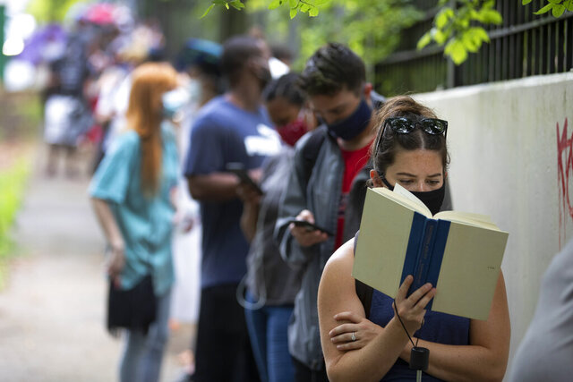 Kelsey Luker reads as she waits in line to vote, Tuesday, June 9, 2020, in Atlanta. Luker said she had been in line for almost two hours. (AP Photo/John Bazemore)