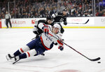 Washington Capitals' Jakub Vrana, bottom, falls as he reaches for the puck in front of Los Angeles Kings' Derek Forbort during the first period of an NHL hockey game Monday, Feb. 18, 2019, in Los Angeles. (AP Photo/Marcio Jose Sanchez)