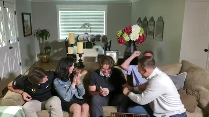 In this still image from video provided by the NFL, Justin Herbert holds his phone during the NFL football draft Thursday, April 23, 2020. The Los Angeles Chargers selected Herbert with the sixth pick. (NFL via AP)
