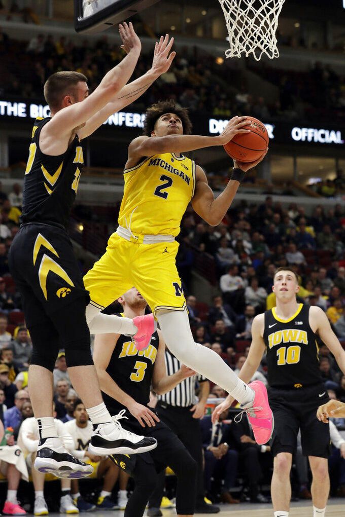 Michigan's Jordan Poole (2) goes up to a basket against Iowa's Connor McCaffery during the second half of an NCAA college basketball game in the quarterfinals of the Big Ten Conference tournament, Friday, March 15, 2019, in Chicago. (AP Photo/Nam Y. Huh)