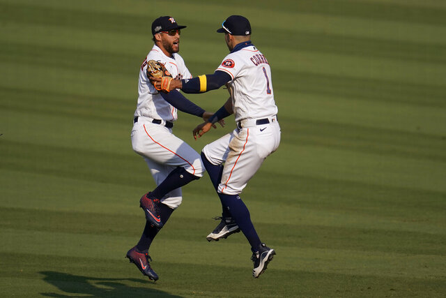 Houston Astros' George Springer, left, celebrates with Carlos Correa after the Astros defeated the Oakland Athletics in Game 4 of a baseball American League Division Series in Los Angeles, Thursday, Oct. 8, 2020. (AP Photo/Marcio Jose Sanchez)