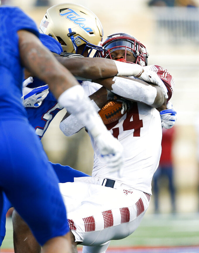 "FILE - In this Nov. 25, 2017, file photo, Temple's David Hood, right, is tackled by the Tulsa defense during an NCAA college football game in Tulsa, Okla. Hood is set to take the field one more time. The running back-turned-rapper will perform at halftime on Thursday night, Sept. 20, at Lincoln Financial Field the new Temple sports anthem he wrote, called ""Temple Made."" (Jessie Wardarski/Tulsa World via AP, File)"
