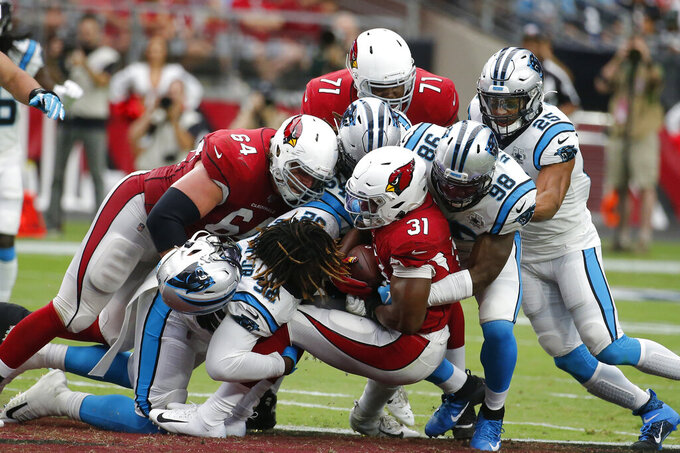 "FILE - In this Sunday, Sept. 22, 2019, file photo, Arizona Cardinals' David Johnson (31) is stopped by the Carolina Panthers defense during an NFL football game in Glendale, Ariz.  You can take that ""any given Sunday"" bromide and toss it out with some of Case Keenum's interceptions. So far in 2019, there is a Grand Canyon of separation between the contenders and everybody else. (AP Photo/Rick Scuteri, File)"