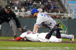 Minnesota Twins' Josh Donaldson, left, beats the tag by Toronto Blue Jays' Breyvic Valera (74) as he dives safely back to third after being caught off the base in the third inning of a baseball game, Thursday, Sept. 23, 2021, in Minneapolis. (AP Photo/Jim Mone)