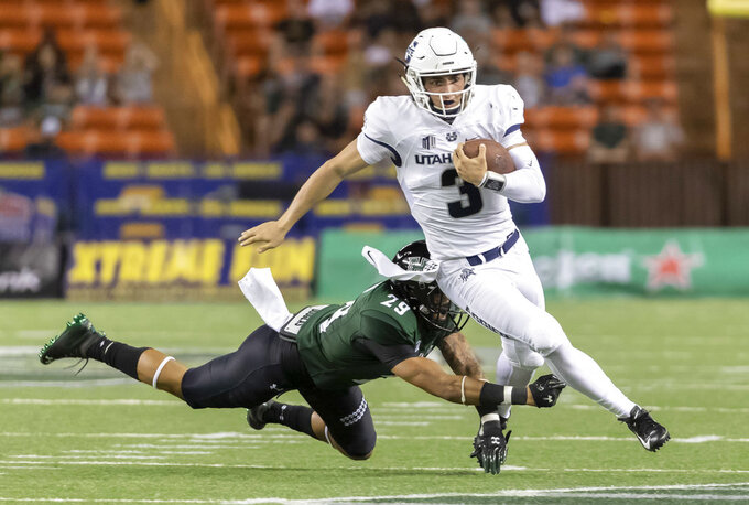 Utah State quarterback Henry Colombi (3) escapes the grasp of Hawaii defensive back Donovan Dalton (29) in the second half of an NCAA college football game, Saturday, Nov. 3, 2018, in Honolulu. (AP Photo/Eugene Tanner)