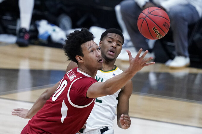 Arkansas forward Jaylin Williams, left, fights for a loose ball with Baylor guard Jared Butler during the first half of an Elite 8 game in the NCAA men's college basketball tournament at Lucas Oil Stadium, Monday, March 29, 2021, in Indianapolis. (AP Photo/Darron Cummings)