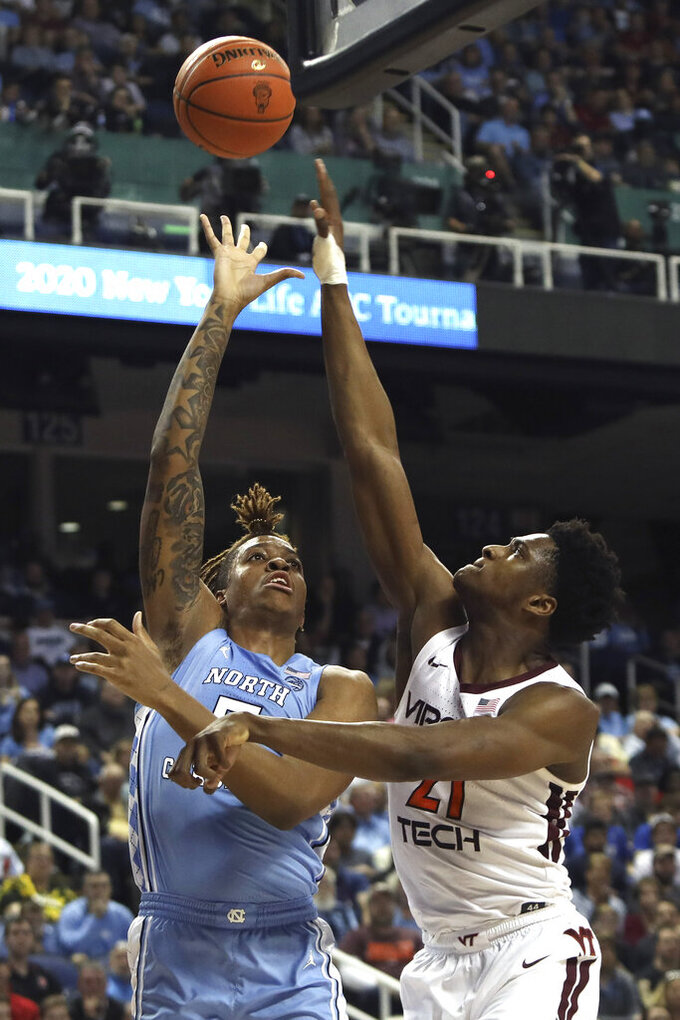 North Carolina forward Armando Bacot (5) shoots over Virginia Tech forward John Ojiako (21) during the first half of an NCAA college basketball game at the Atlantic Coast Conference tournament in Greensboro, N.C., Tuesday, March 10, 2020. (AP Photo/Ben McKeown)