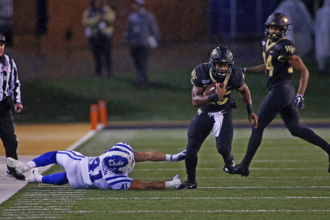 Wake Forest running back Kenneth Walker III, center, breaks free from Duke linebacker Xander Gagnon as he carries the football in the first half of an NCAA college football game in Winston-Salem, N.C., Saturday, Nov. 23, 2019. (AP Photo/Nell Redmond)