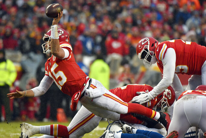 Kansas City Chiefs quarterback Patrick Mahomes (15) attempts to throw away the ball as he is tackled by an Indianapolis Colts defender during the first half of an NFL divisional football playoff game in Kansas City, Mo., Saturday, Jan. 12, 2019. (AP Photo/Ed Zurga)