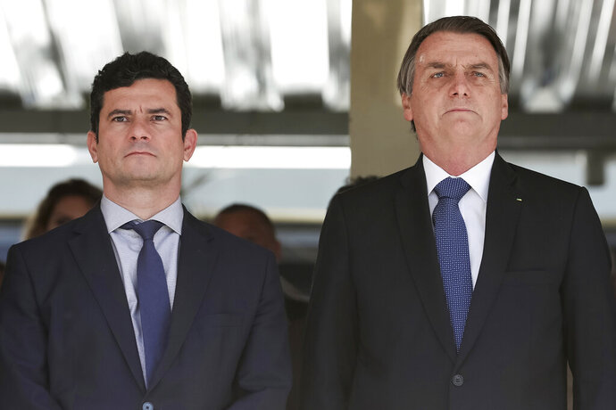 In this photo released by Brazil's Presidential Press Office, Brazil's President Jair Bolsonaro, right, and Justice Minister Sergio Moro attend a military ceremony in Brasilia, Brazil, Tuesday, June 11, 2019. Moro has met with President Jair Bolsonaro, two days after press reports accused him of allegedly coordinating with prosecutors when he was a judge. (Marcos Correa/Brazil's Presidential Press Office via AP)