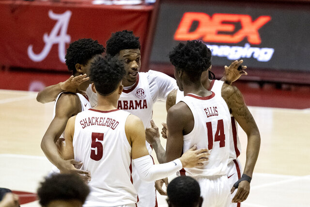 Alabama's Herbert Jones puts his arms around teammates in the final minute of Alabama's NCAA college basketball game against Mississippi State, Saturday, Jan. 23, 2021, in Tuscaloosa, Ala. (AP Photo/Vasha Hunt)