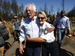 Democratic presidential candidate Sen. Bernie Sanders, I-Vermont, is hugged by Geralynne Radar, a volunteer with the Paradise Police Department, as he tours a mobile home park destroyed by last year's wildfire fire in Paradise, Calif., Thursday, Aug. 22, 2019. (AP Photo/Rich Pedroncelli)