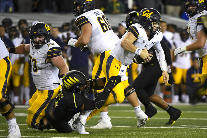California quarterback Chase Garbers (7) works to escape the grasp of Oregon defensive end Kayvon Thibodeaux (5) during the fourth quarter of an NCAA college football game Friday, Oct. 15, 2021, in Eugene, Ore. (AP Photo/Andy Nelson)