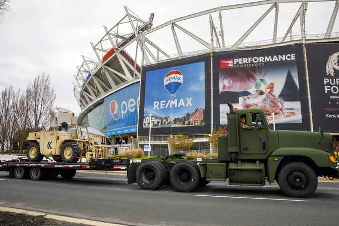 Equipment is driven by FedEx Field as the National Guard sets up tents to be used for coronavirus testing, Saturday, March 21, 2020, in a parking lot at the NFL football stadium in Landover, Md., outside of Washington. (AP Photo/Jacquelyn Martin)