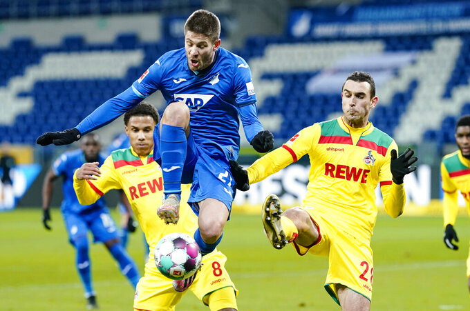 Cologne's Ismail Jakobs, left, and Ellyes Skhiri challenges Hoffenheim's Andrej Kramaric for the ball during the  Bundesliga soccer match between Hoffenheim and Cologne at PreZero Arena in Sinsheim, Germany, Sunday Jan. 24, 2021. (Uwe Anspach/dpa via AP)