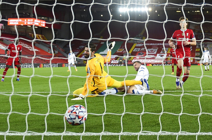 Atalanta's Josip Ilicic, center right, scores the opening goal past Liverpool's goalkeeper Alisson, center left, during the Champions League group D soccer match between Liverpool and Atalanta at Anfield stadium in Liverpool, England, Wednesday, Nov. 25, 2020. (Laurence Griffiths/Pool via AP)