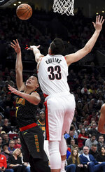 Atlanta Hawks guard Jeremy Lin, left, shoots over Portland Trail Blazers forward Zach Collins during the first half of an NBA basketball game in Portland, Ore., Saturday, Jan. 26, 2019. (AP Photo/Steve Dykes)