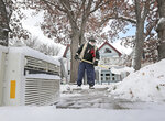 Working next to a discarded air conditioner awaiting recycling, Tom Jacobson shovels away the area's latest accumulation of snow in front of his property in Madison, Wis., Monday, Nov. 11, 2019. (John Hart/Wisconsin State Journal via AP)