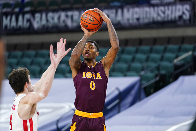 Iona's Berrick JeanLouis, right, goes up for a shot against Fairfield's Jake Wojcik in the first half of an NCAA college basketball game during the finals of the Metro Atlantic Athletic Conference tournament, Saturday, March 13, 2021, in Atlantic City, N.J. (AP Photo/Matt Slocum)
