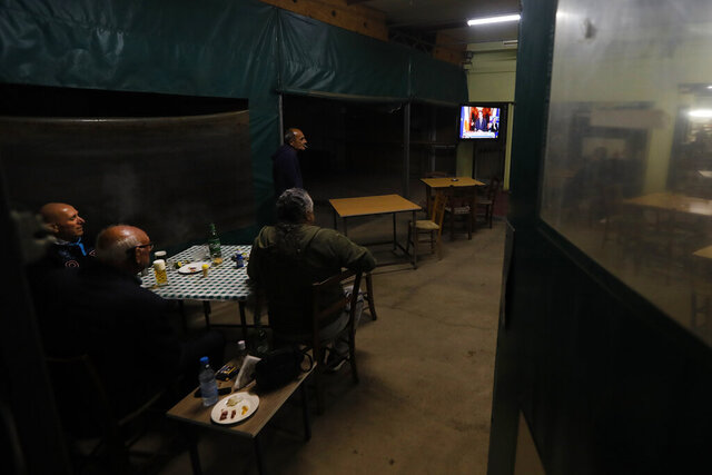 Cypriot men sit at a social club and watch the televised address of Cypriot President Nicos Anastasiades explaining the need for additional restrictions to beat back a surge in COVID-19 cases in Nicosia suburb of Lakatamia, Cyprus, on Tuesday, Nov. 11, 2020. Cyprus has put its entire southwest under a strict 19-day lockdown, banning any non-essential movement of people and shuttering bars and restaurants after a string of escalating restrictions failed to curb a sharp increase in COVID-19 infections. (AP Photo/Petros Karadjias)