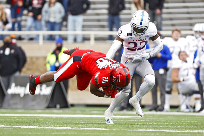 Kansas' Duece Mayberry (22) tackles Texas Tech's Tahj Brooks (28) during the second half of an NCAA college football game Saturday, Dec. 5, 2020, in Lubbock, Texas. (AP Photo/Brad Tollefson)