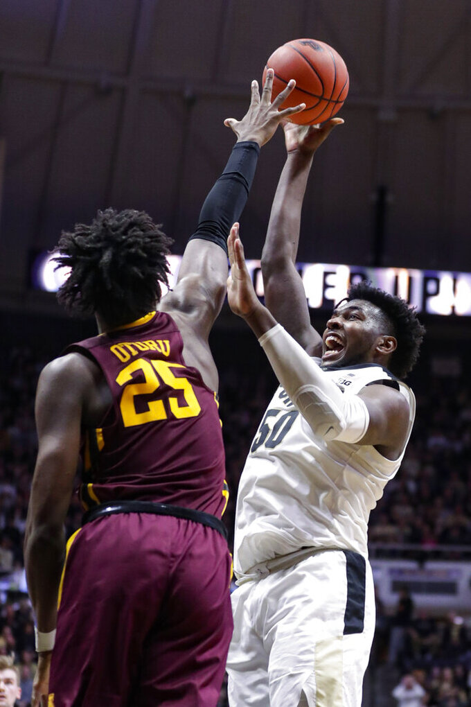 Purdue forward Trevion Williams (50 shoots over Minnesota center Daniel Oturu (25) during the second half of an NCAA college basketball game in West Lafayette, Ind., Thursday, Jan. 2, 2020. Purdue defeated Minnesota 83-78 in double overtime. (AP Photo/Michael Conroy)
