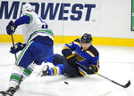 St. Louis Blues' Jaden Schwartz (17) battles for the puck with Vancouver Canucks' Tyler Myers (57) during the first period of an NHL hockey game, Thursday, Oct. 17, 2019, in St. Louis. (AP Photo/Bill Boyce)
