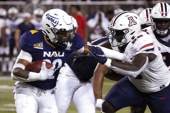 Northern Arizona running back Kevin Daniels (22) stiff arms Arizona defensive lineman Mo Diallo during the first half of an NCAA college football game, Saturday, Sept. 18, 2021, in Tucson, Ariz. (AP Photo/Rick Scuteri)
