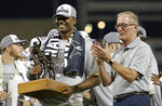 Vanderbilt's Kumar Rocker, left, accepts the tournament Most Outstanding Player award from College World Series President Jack Diesing Jr., right, after Vanderbilt defeated Michigan to win Game 3 of the NCAA College World Series baseball finals in Omaha, Neb., Wednesday, June 26, 2019. (AP Photo/Nati Harnik)