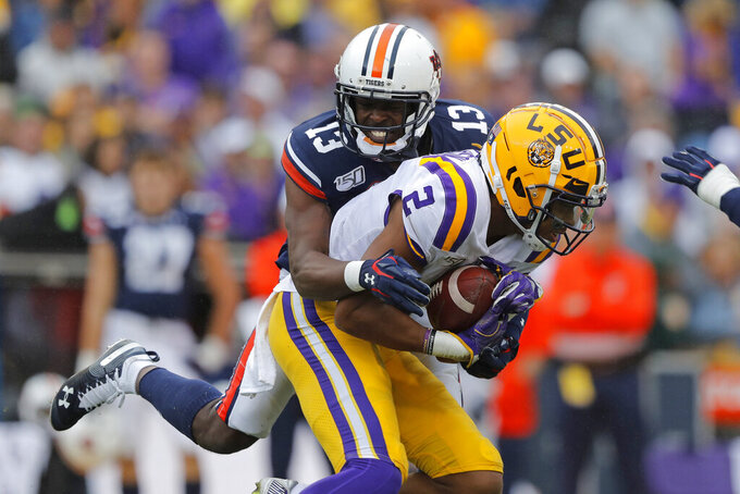 Auburn defensive back Javaris Davis (13) tackles LSU wide receiver Justin Jefferson (2) in the first half of an NCAA college football game in Baton Rouge, La., Saturday, Oct. 26, 2019. (AP Photo/Gerald Herbert)
