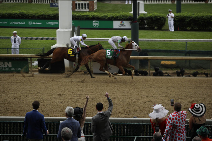 People cheer as they watch a race at Churchill Downs before the 145th running of the Kentucky Derby horse race Saturday, May 4, 2019, in Louisville, Ky. (AP Photo/Charlie Riedel)