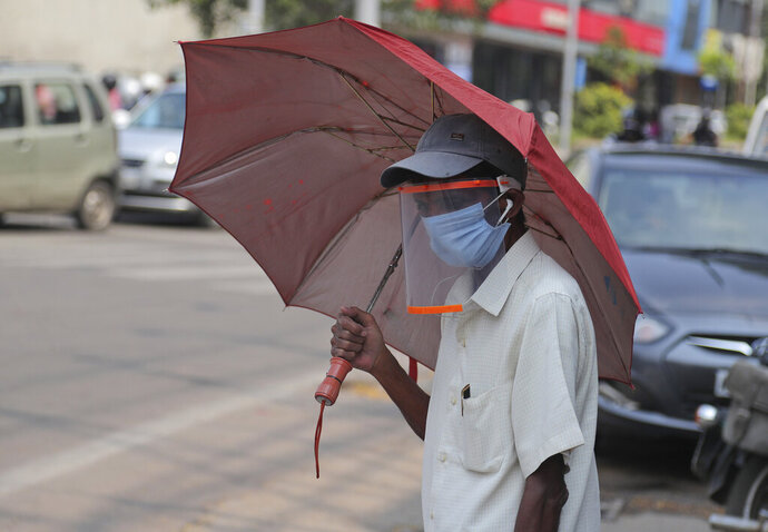 A man wearing a face shield as a precautionary measure against the coronavirus walks on a street in Hyderabad, India, Tuesday, Oct. 27, 2020. India reports 36,470 new coronavirus cases, the lowest in more than three months in a continuing downward trend. However, the overall tally neared 8 million, the second in the world behind the U.S. with over 8.7 million positive cases. (AP Photo/Mahesh Kumar A.)