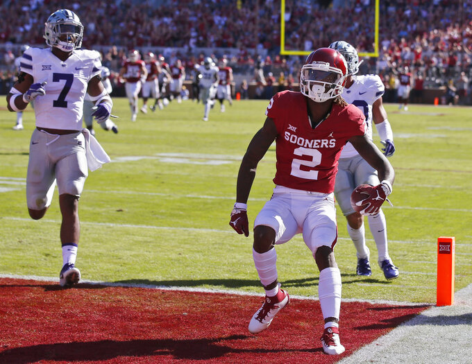 Oklahoma wide receiver CeeDee Lamb (2) scores in front of Kansas State defensive back Eli Walker (7) and defensive back Denzel Goolsby, right, in the first half of an NCAA college football game in Norman, Okla., Saturday, Oct. 27, 2018. (AP Photo/Sue Ogrocki)