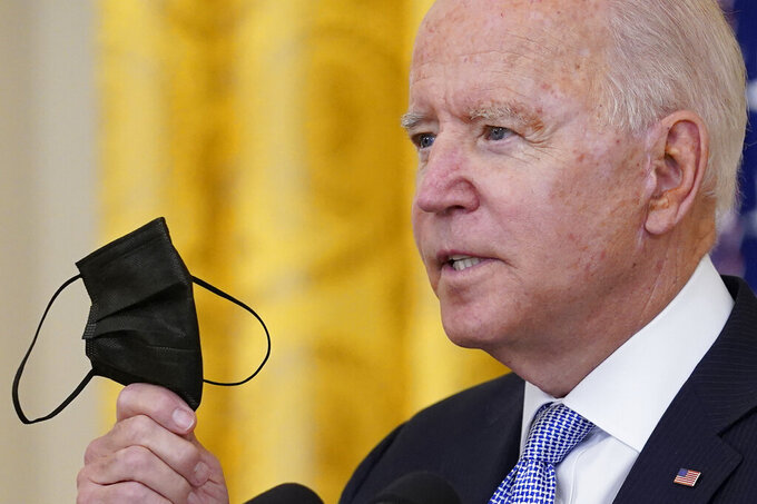 President Joe Biden holds up his face mask as he speaks about vaccine requirements for federal workers in the East Room of the White House in Washington, Thursday, July 29, 2021. (AP Photo/Susan Walsh)
