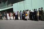 Afghans wait in long lines for hours  to get visas in front of the Iranian embassy, in Kabul, Afghanistan, Sunday, Aug. 15, 2021. Officials say Taliban fighters have entered Kabul and are seeking the unconditional surrender of the central government. (AP Photo/Rahmat Gul)