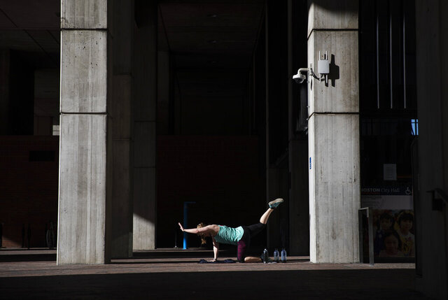 Unable to work out at her gym since it closed due to coronavirus, a woman exercises in a quiet corner at the entrance to City Hall, Saturday, March 21, 2020, in Boston. For some people the COVID-19 coronavirus causes mild or moderate symptoms, but for some it causes severe illness. (AP Photo/David Goldman)