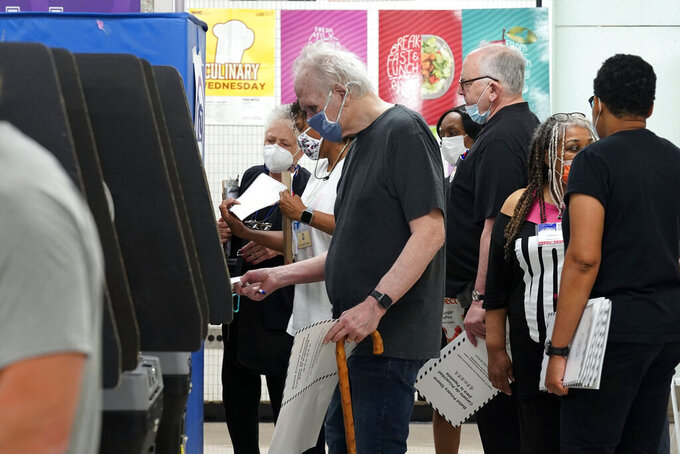 Voters place their marked ballots in scanners at Frank McCourt High School, in New York, Tuesday, June 22, 2021. The final votes are set to be cast Tuesday in New York's party primaries, where mayors, prosecutors, judges and city and county legislators will be on the ballot, along with other municipal offices. (AP Photo/Richard Drew)