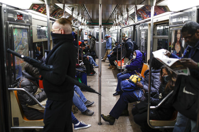 """Subway customers wears masks on a crowded car heading downtown, Tuesday, March 17, 2020, in New York. Mayor Bill de Blasio said New York City residents should be prepared for the possibility of a """"shelter in place"""" order within days. De Blasio said Tuesday no decision had been made yet, but he wants city and state officials to make a decision within 48 hours given given the fast spread of the coronavirus. (AP Photo/John Minchillo)"""